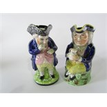 Two 19th century Staffordshire Toby jugs, one in the form of a standing blue jacketed Toby with a