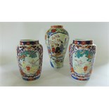 A pair of late 19th century Imari vases tapering cylindrical form each with two polychrome painted