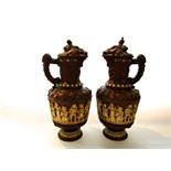 A pair of late 19th century large German relief moulded ewers and covers with decoration of