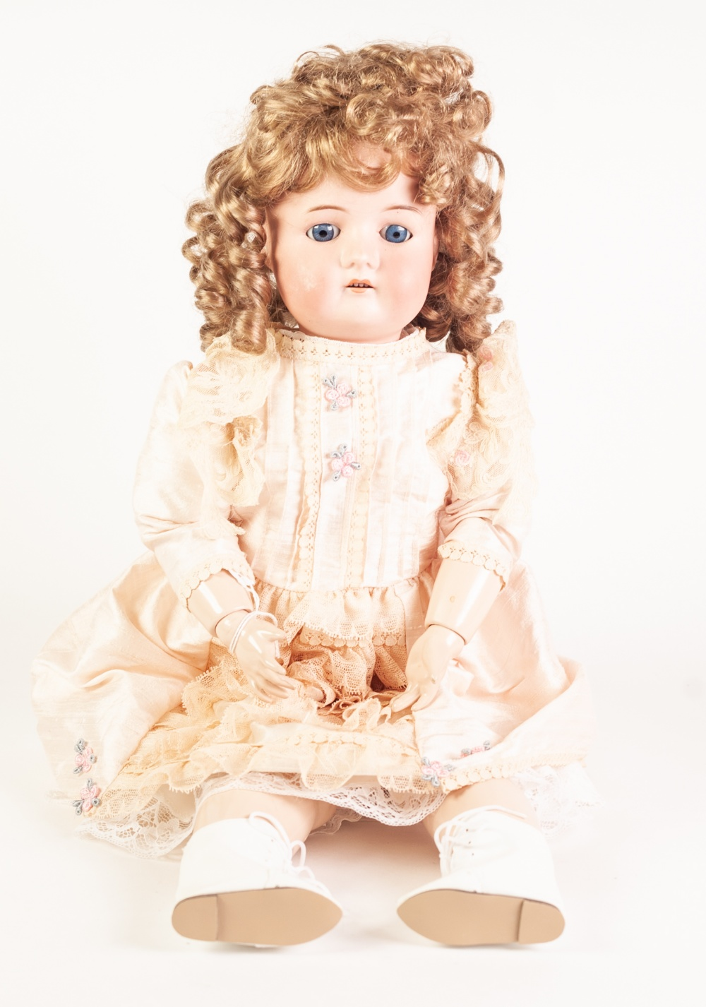 Lot 303 - A GERMAN BISQUE HEAD DOLL, with fixed blue eyes and open mouth, on later ball jointed composition