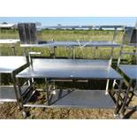 Stainless steel mobile food preparation station with 2 shelves over, shelf under space for trays,