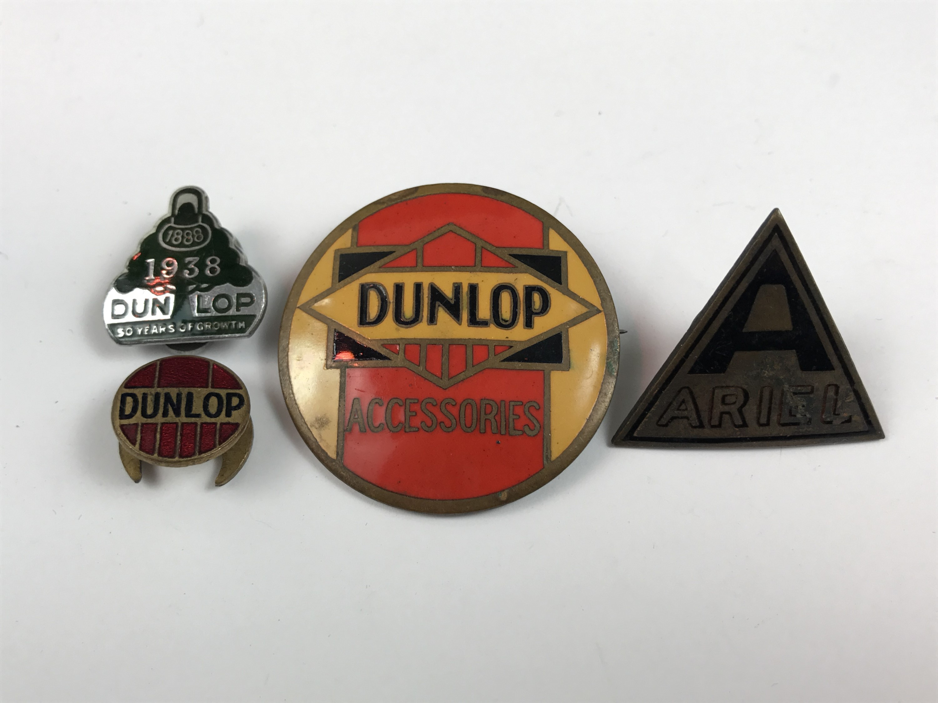 Lot 37 - [Classic cars / motorcycles] Four various enamelled lapel badges, advertising Dunlop Tyres and Ariel