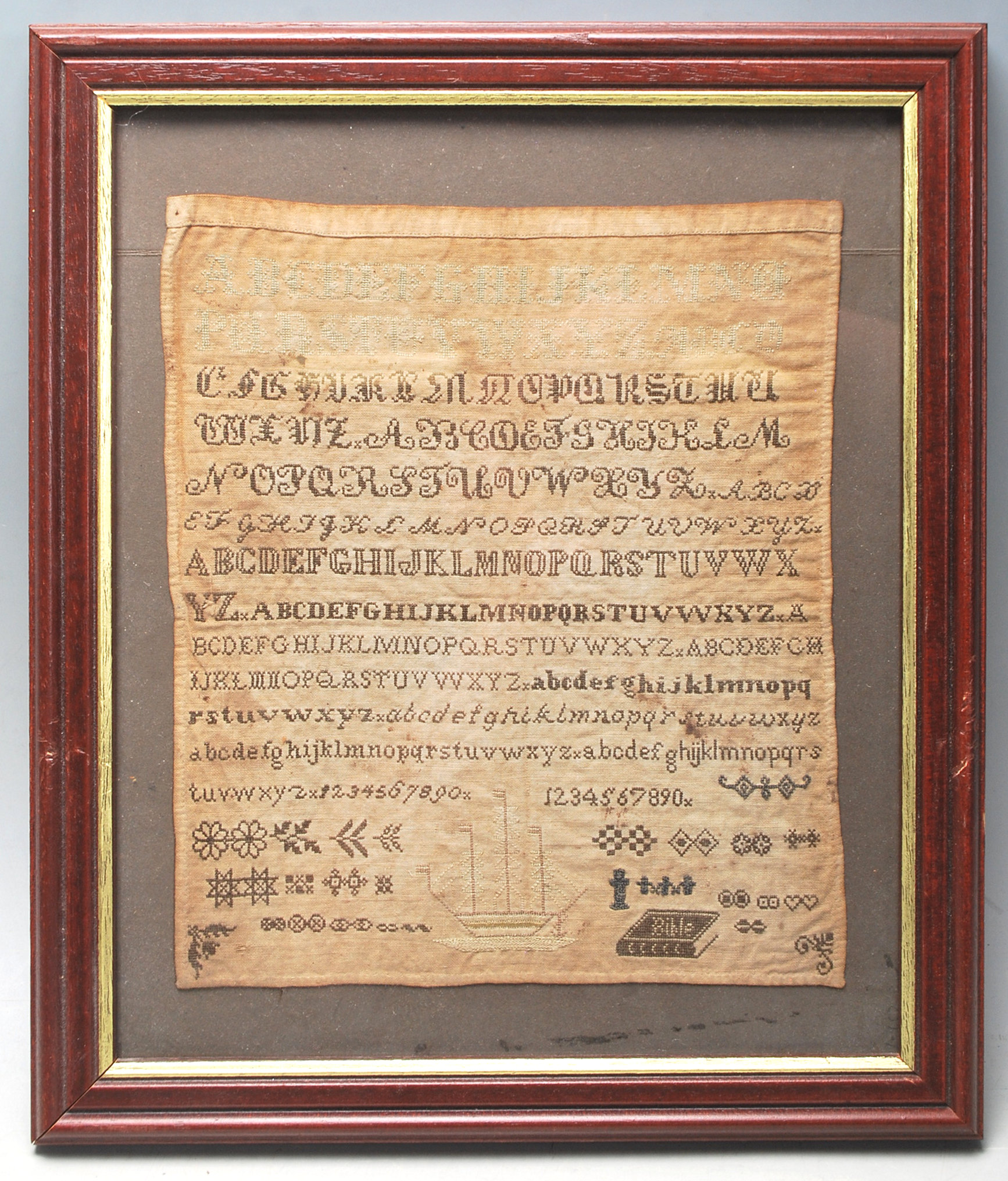 A 19th Century Victorian needlework / needlepoint embroidery sampler stitched with the alphabet,