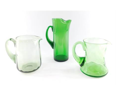 A Whitefriars green glass water jug, 26cm high., fluted green glass jug, 17cm high., and a green glass jug with wavy banding,