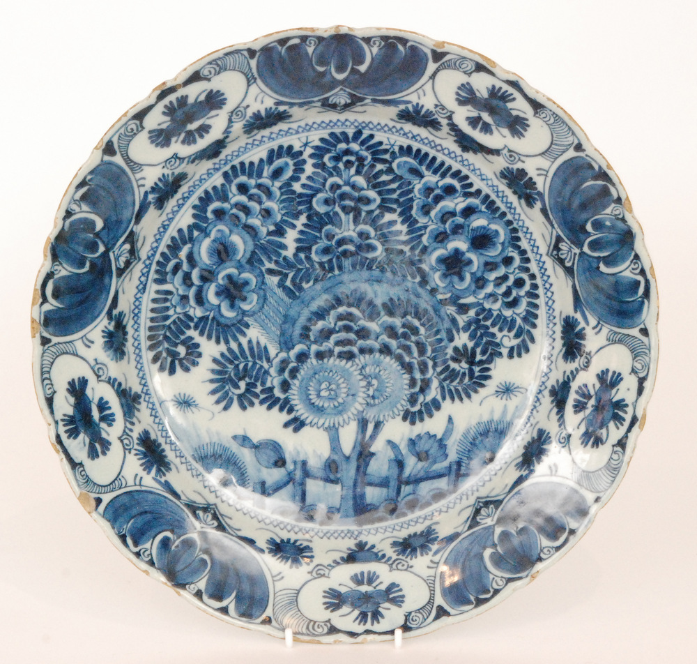 Lot 36 - A late 19th Century Delft tin glaze plate decorated in blue and white with a large spray of flowers
