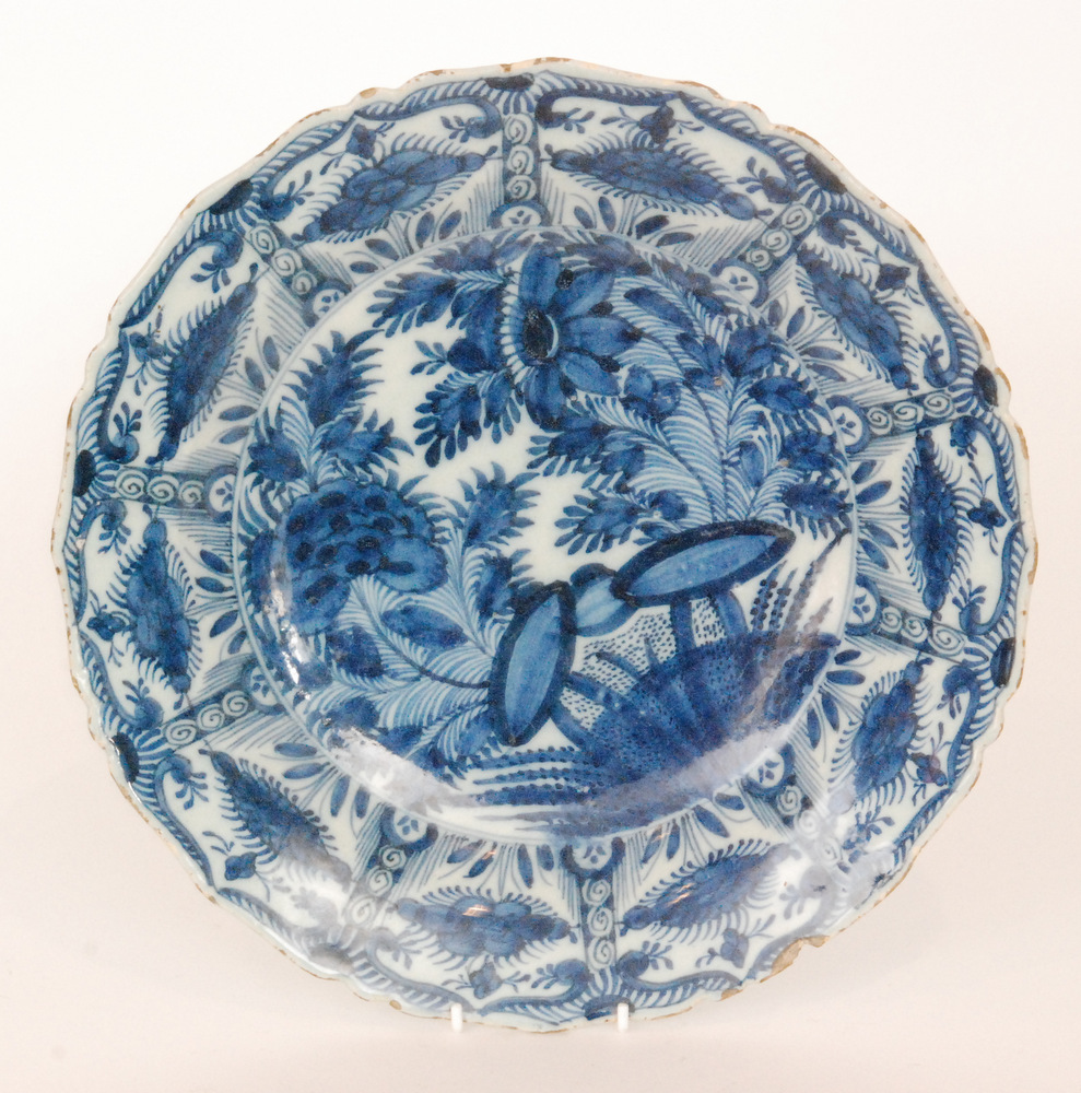 Lot 35 - A late 19th Century Delft tin glaze plate decorated in blue and white with a large spray of flowers