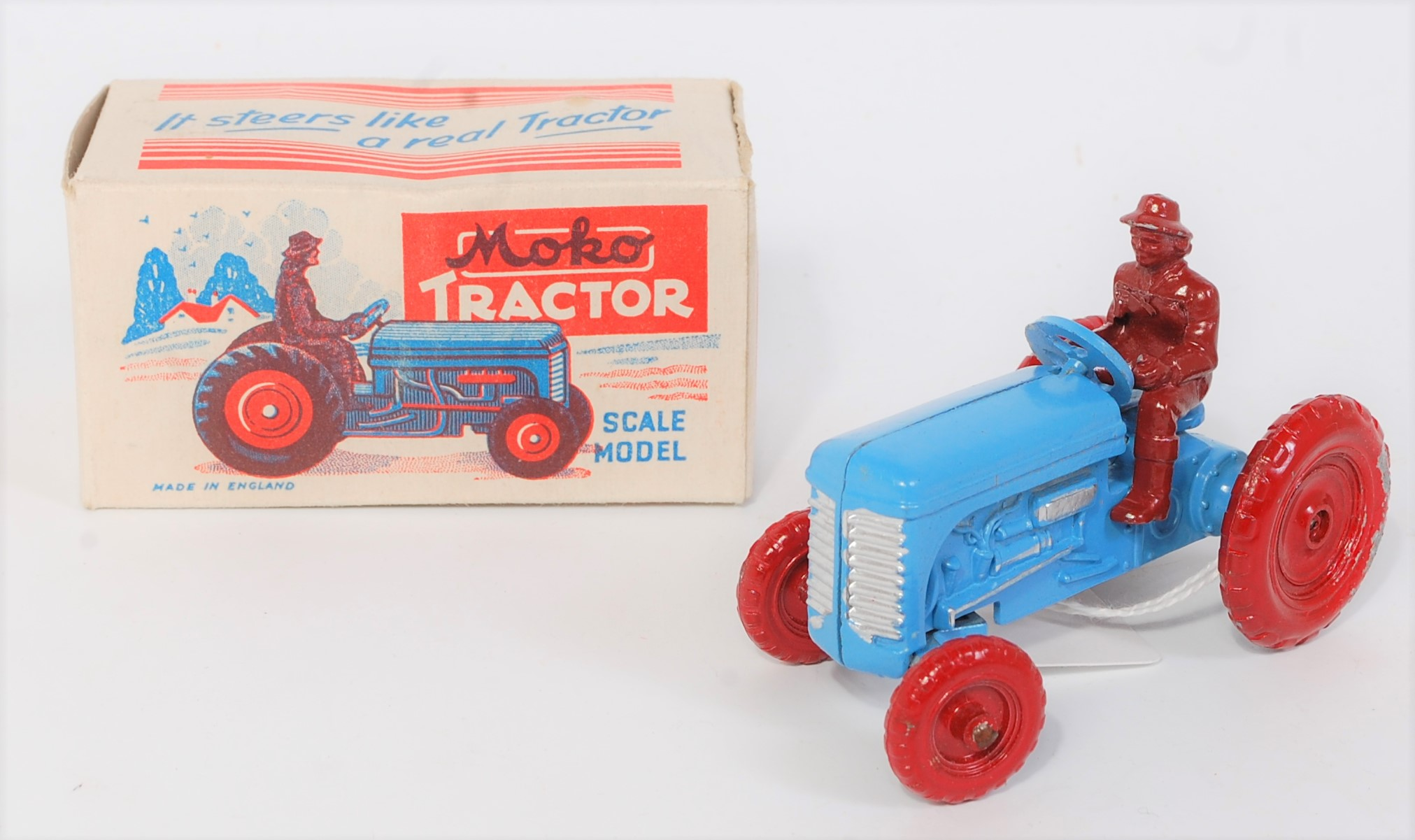 A Moko Products scale model of a tractor finished in red and blue with dark red driver figure,