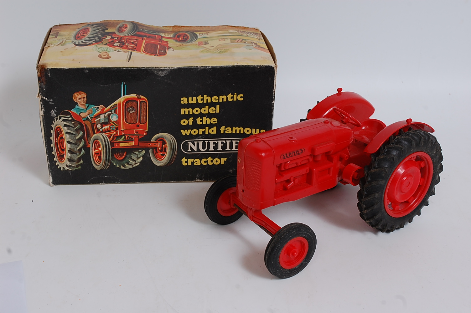 A Pippin Toys large scale plastic model of a Nuffield tractor, comprising of red body with