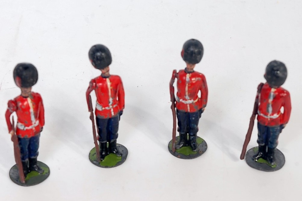 Four various Britains from set No. 111 round based Grenadier guards, some signs of overpainting, one