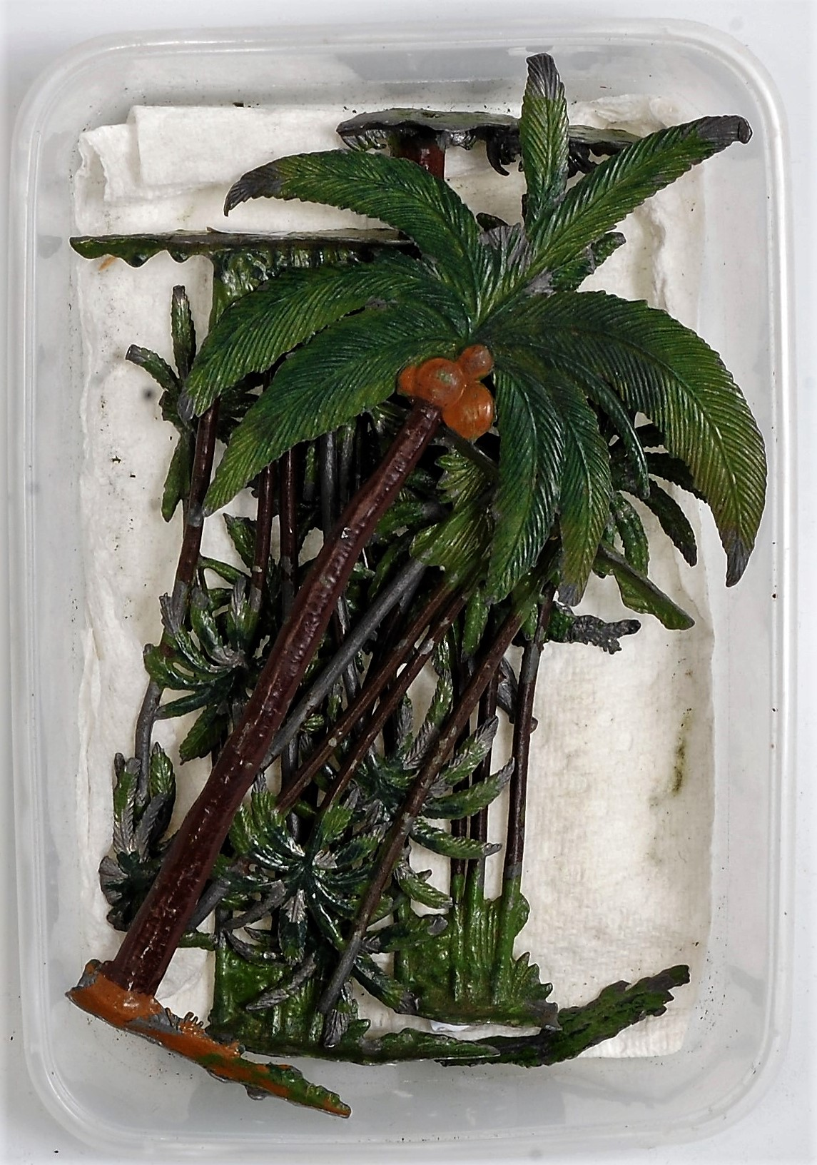 A small tray containing a quantity of various Britains palm and exotic trees, all with minor