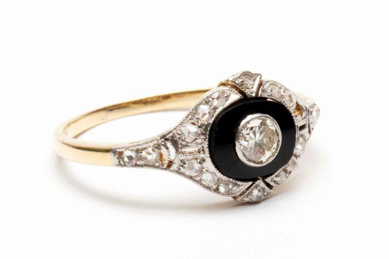 Lot 42 - Geel- en witgouden ring, ca. 1920,gezet met een ovale onyx, met in het midden een briljant