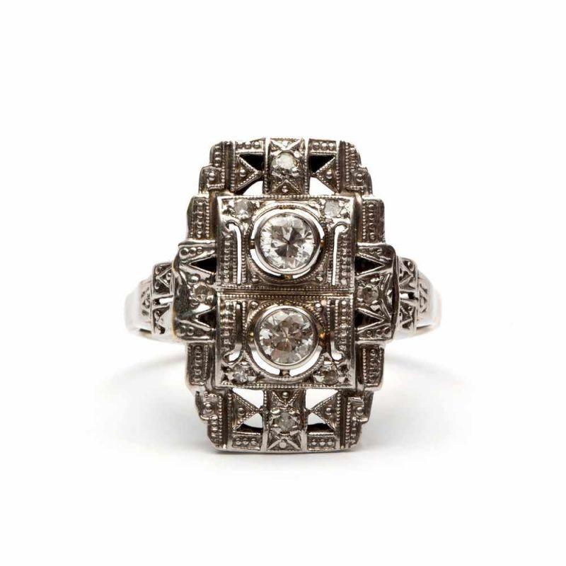 Lot 54 - Witgouden appliqueringgezet met twee briljant geslepen diamanten, totaal ca. 0,35crt. Kop