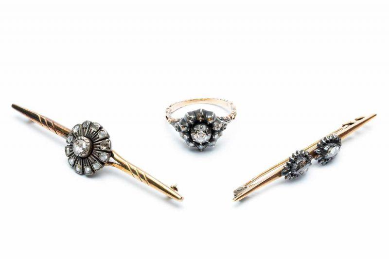 Lot 31 - Zilveren en gouden rozetring en twee staafbroches.Ring in het midden gezet met een roosdiamant, in