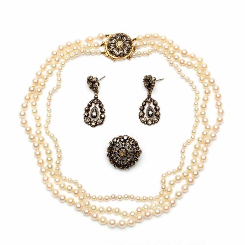 Lot 30 - Paar zilveren en gouden oorhangers, drierijig parelcollier en een zilveren brochealle gezet met