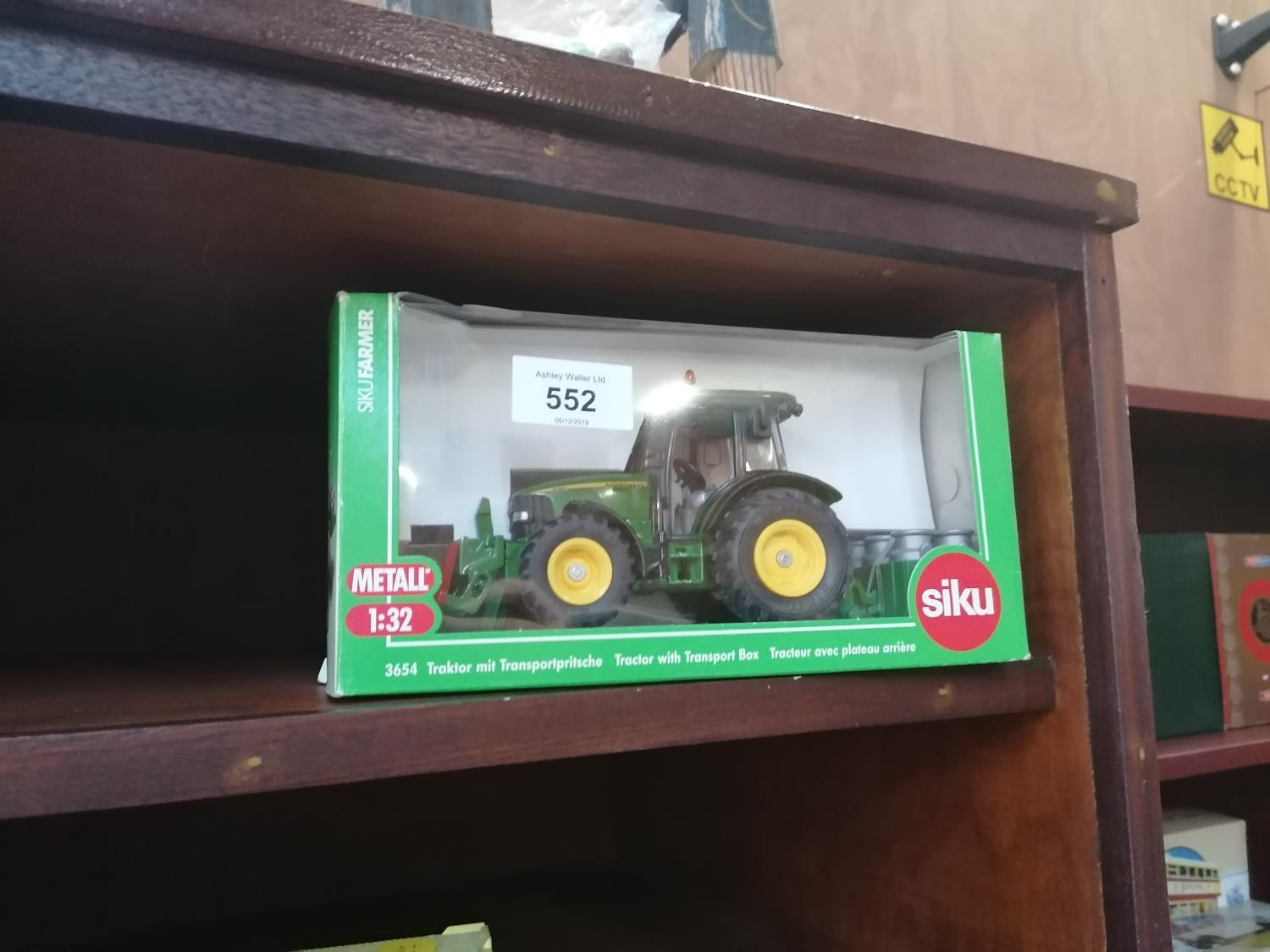 Lot 552 - A SIKU 1:32 SCALE TRACTOR MODEL WITH MILK CHURNS