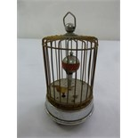 Lot 224 - An automation clock with bird in a cage with carrying handle on circular base