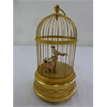 Lot 222 - Swiss Automation two singing birds in a gilded metal cage with circular carrying handle on three