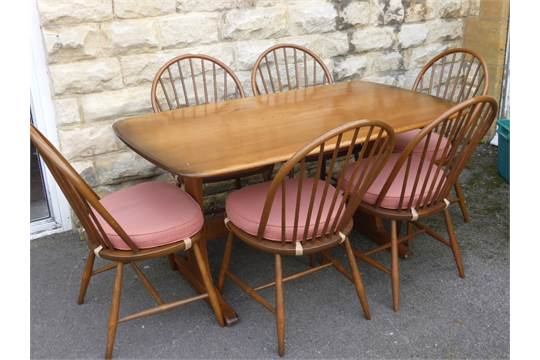 An Ercol Autumn Gold Dining Table With Six Latimer Spindle Back Dining Chairs
