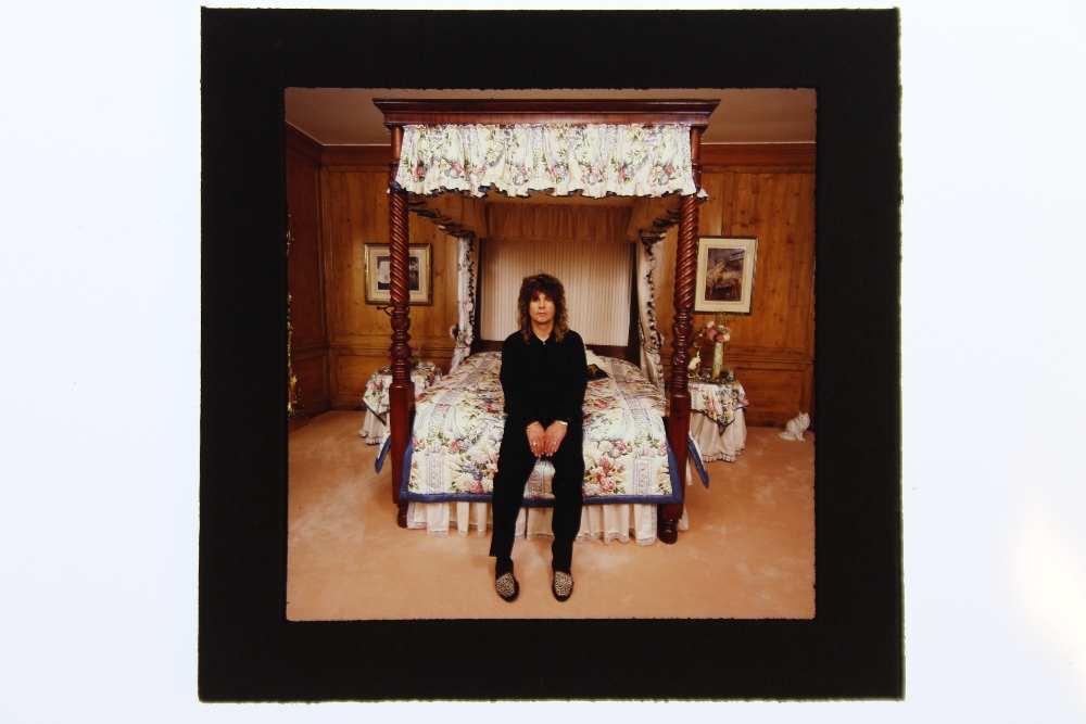Lot 139 - OZZY OSBOURNE - a mounted negative of Ozzy Osbourne seated on a four poster bed in Beel House,