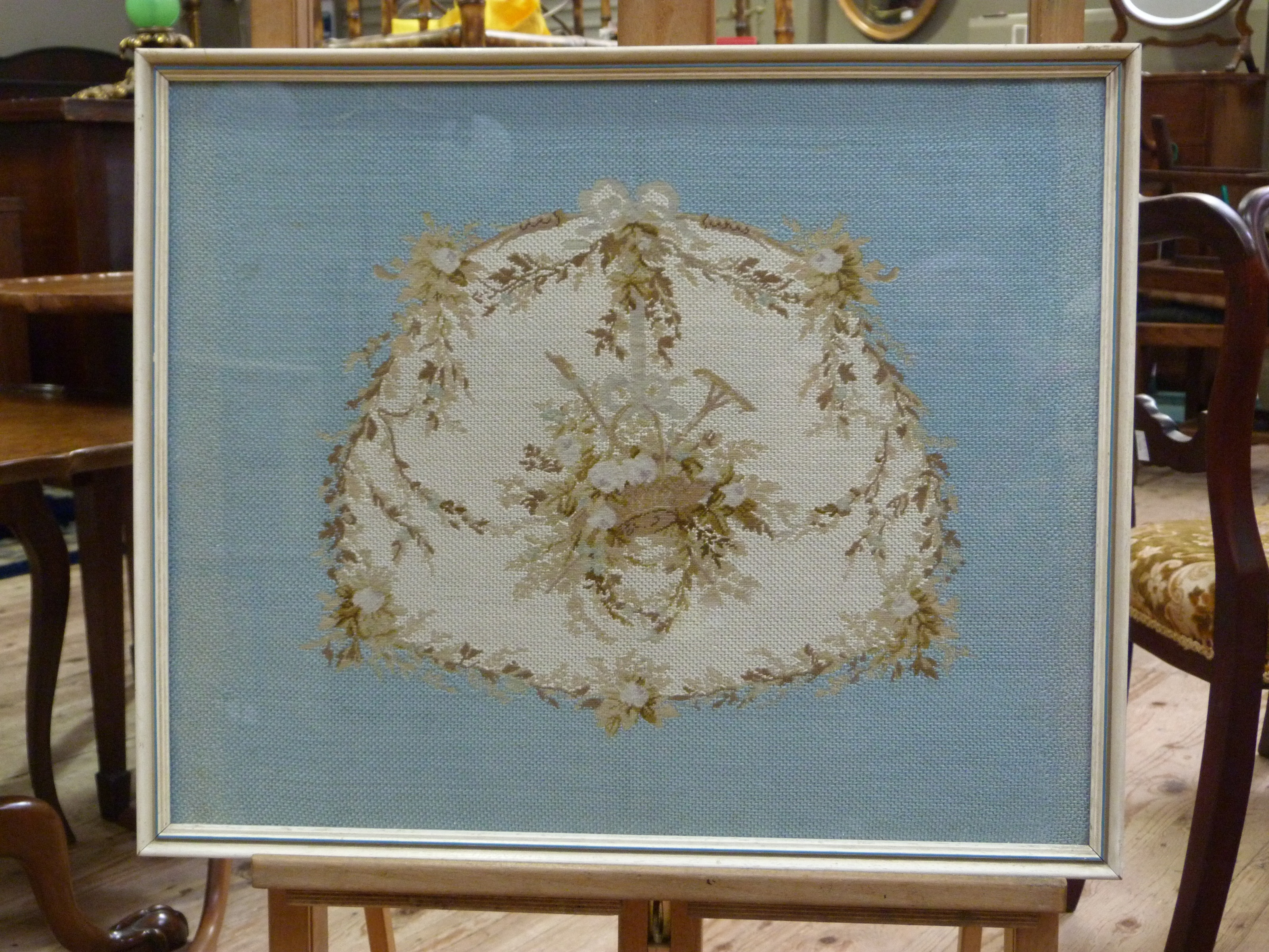 Lot 224 - An early 20th century needlework panel depicting a basket of flowers, rake and hoe within a