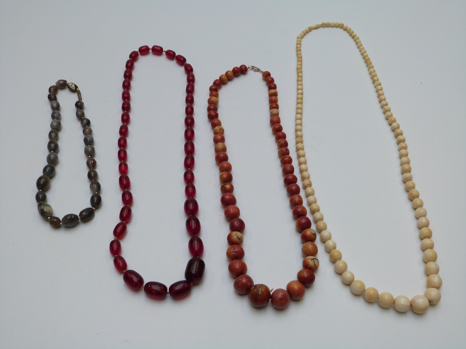 Lot 30 - A collection of necklaces including early 20thC ivory, coral, cherry amber, gold plated, agate etc