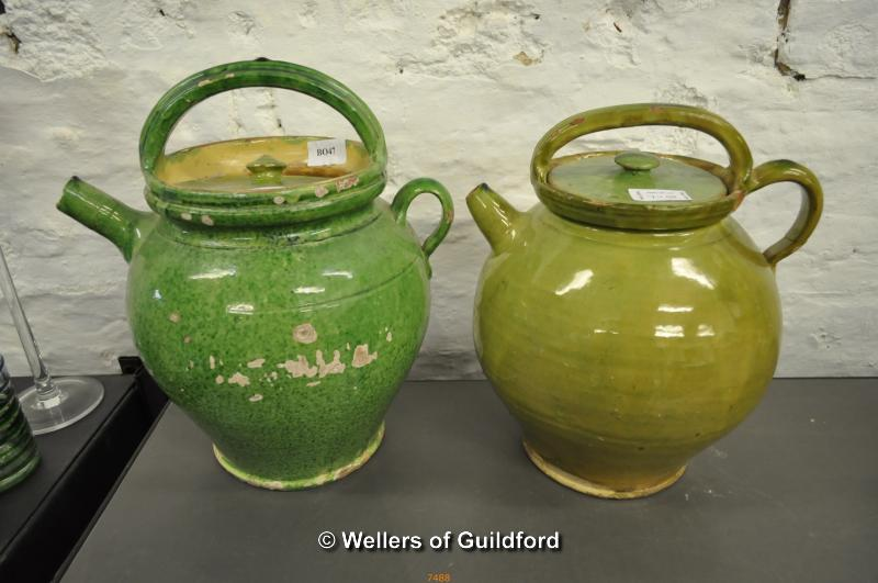 Lot 7488 - Two French pottery lidded jugs in green glaze, the largest 33cm.