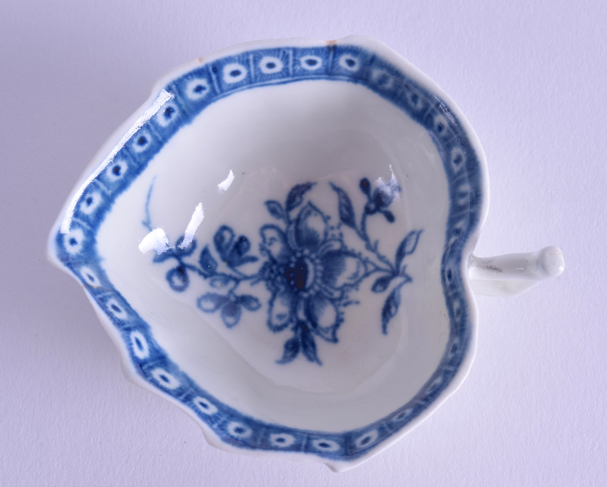 Lot 132 - 18th c, Worcester leaf shaped twig handled butterboat with floral centre and cell border in under