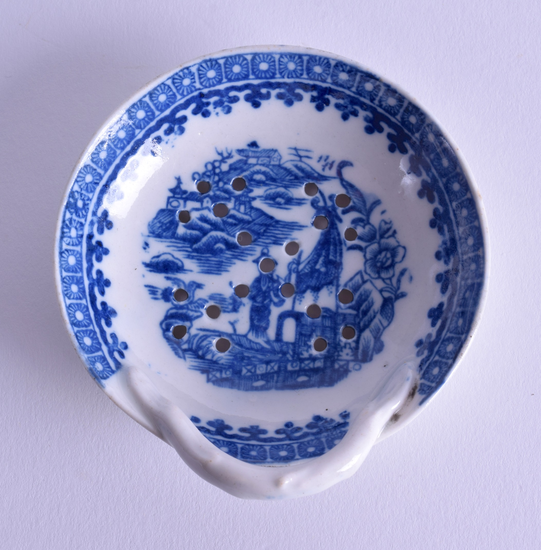 Lot 150 - 18th c. Caughley egg drainer printed with the Fisherman pattern in blue. 8.5cm diameter