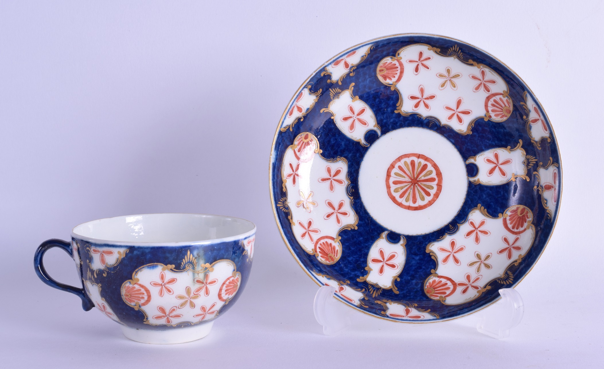 Lot 141 - 18th c. Worcester teacup and saucer painted with the Old Japan Star pattern on a blue scale