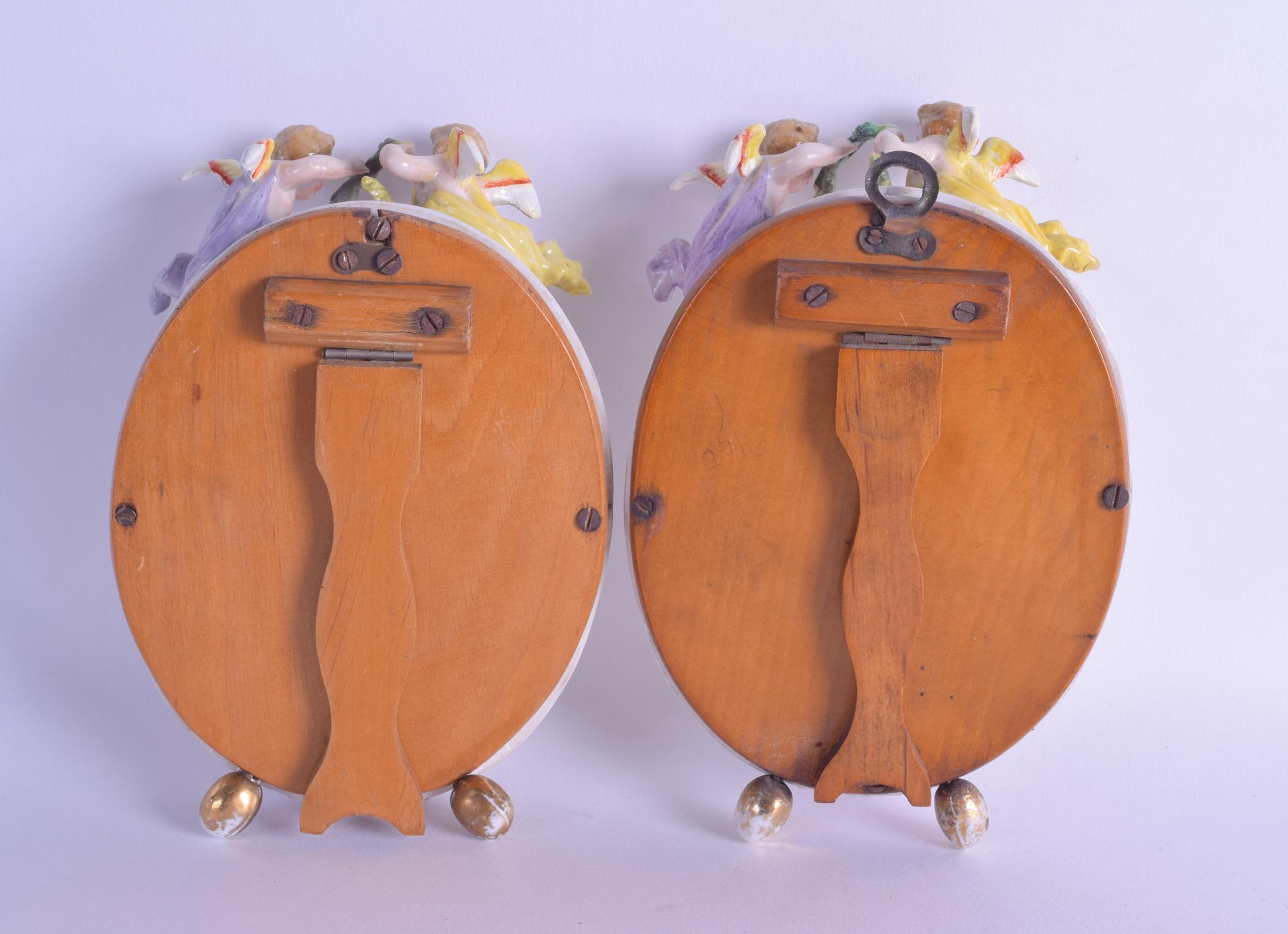 Lot 155 - 19th c. Sitzendorf pair of table mirror surmounted by winged cherubs. 16cm high