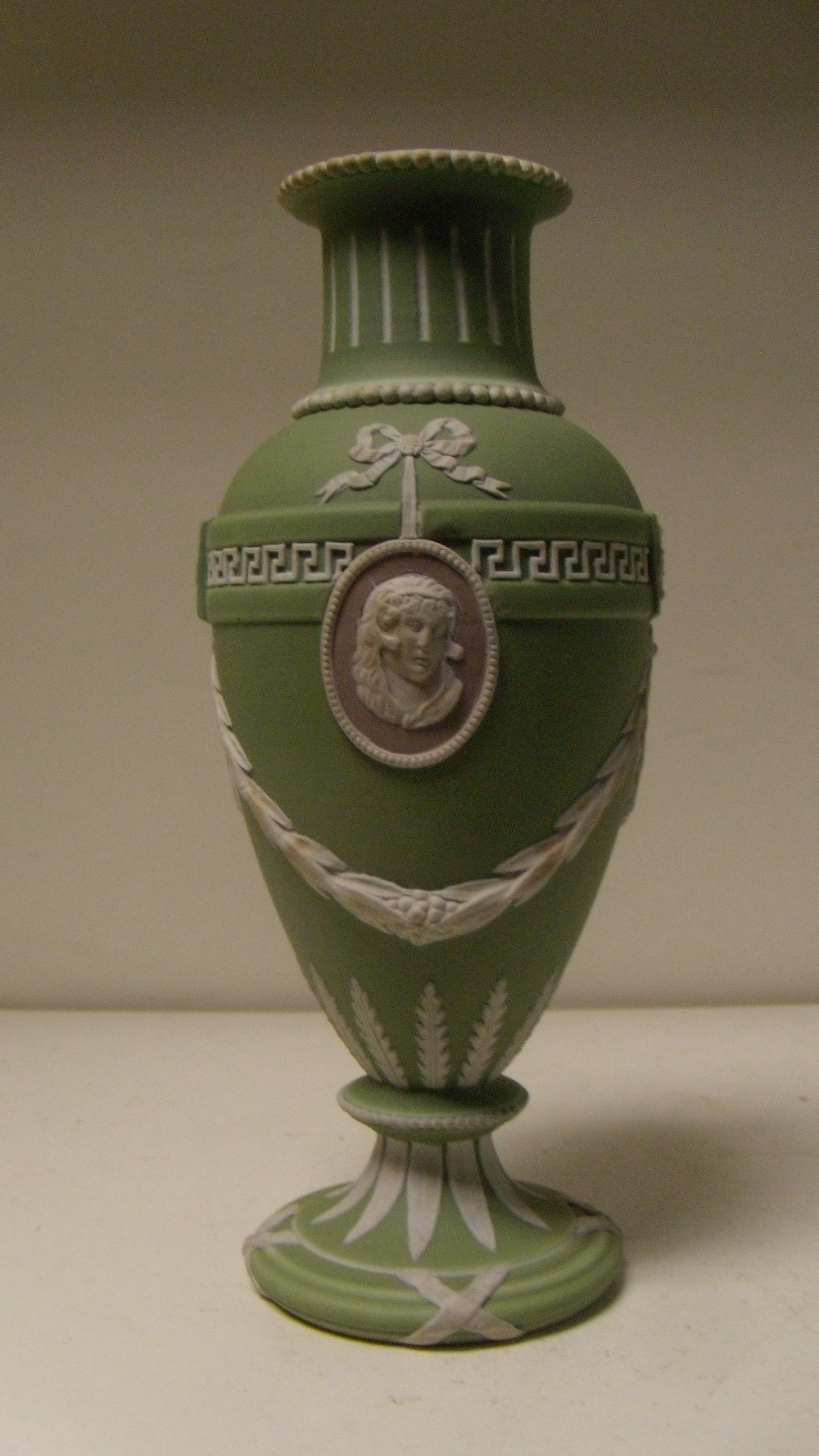 Lot 2 - A Wedgwood three colour jasper vase, the green ovoid body with two classical profiles in white on