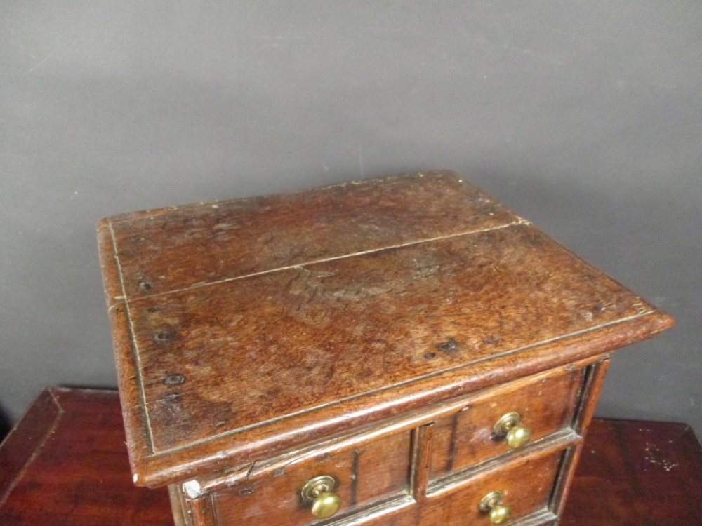 Lot 719 - A small 17th century oak chest, a hinged top with false drawer fronts and brass handles, on later