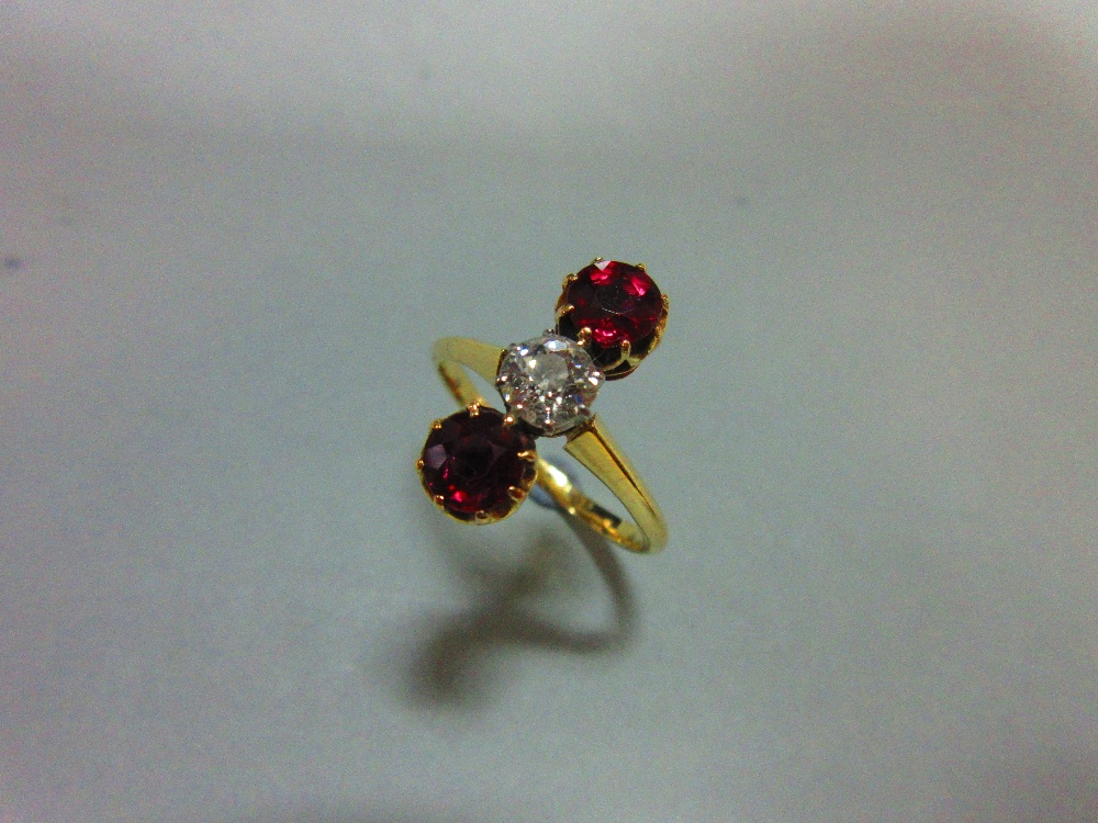 Lot 190 - A ruby and diamond three stone ring, the vertically set stones being an old round brilliant cut