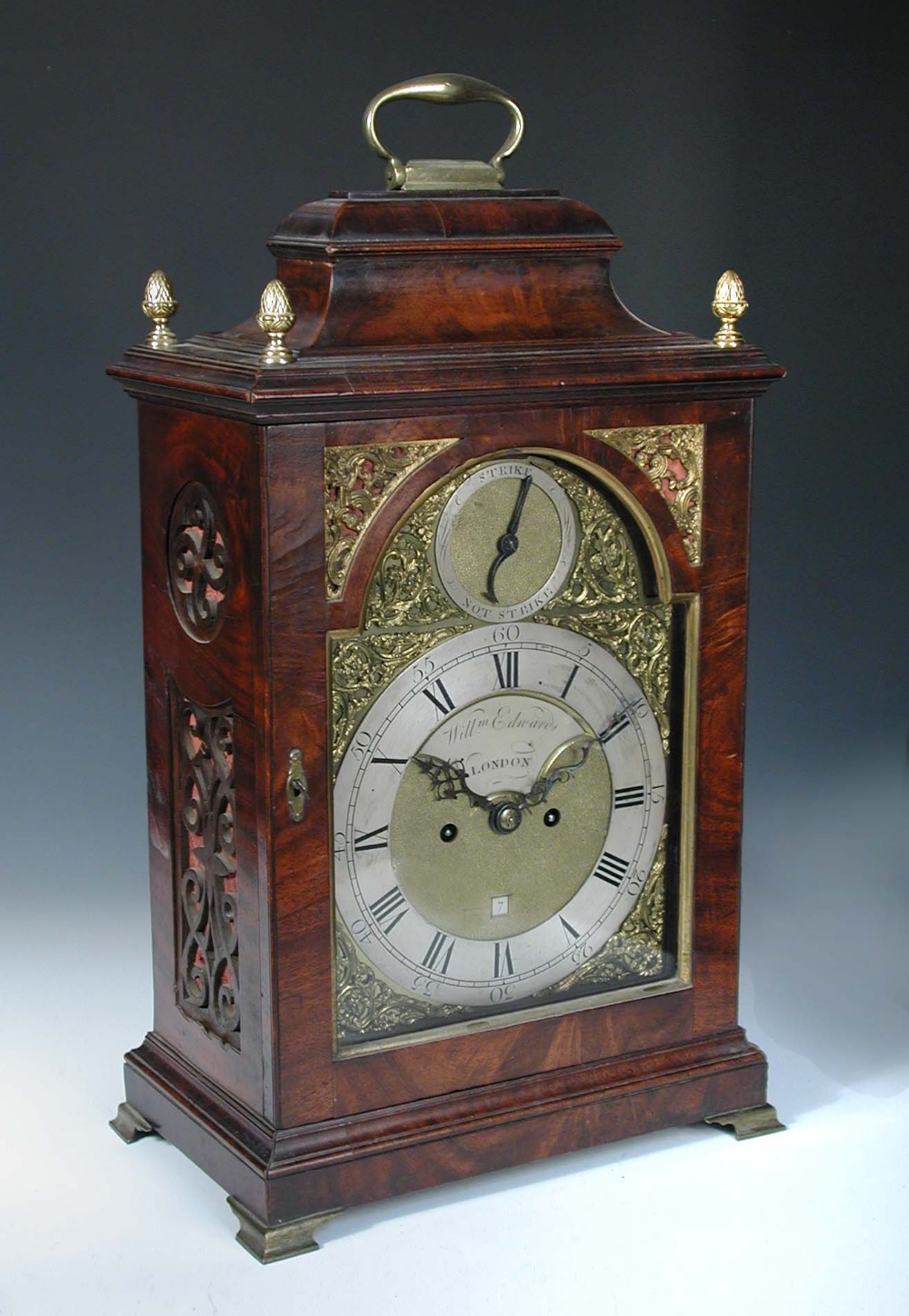 Lot 686 - A George III mahogany bracket clock, the bell top case with brass handle and four gilt finials above