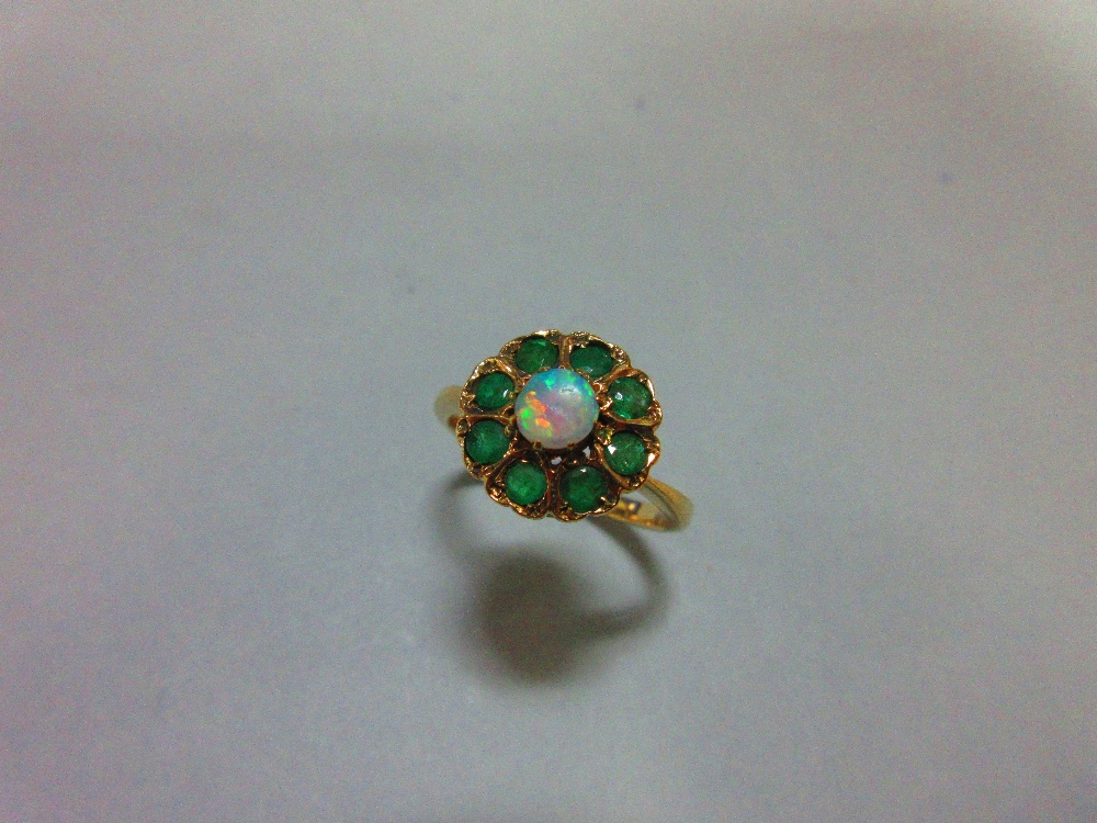Lot 200 - An opal and emerald cluster ring, with a round cabochon opal centre in a border of eight round cut