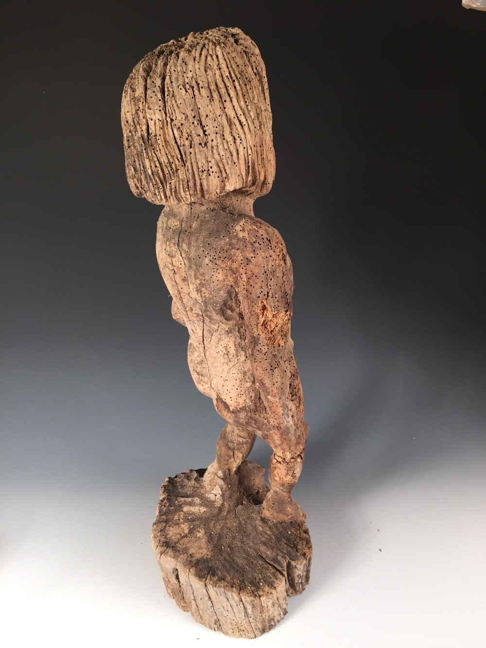 Lot 656 - A Mediaeval style carved wood figure, possibly of Adam, the bearded figure naked with his left