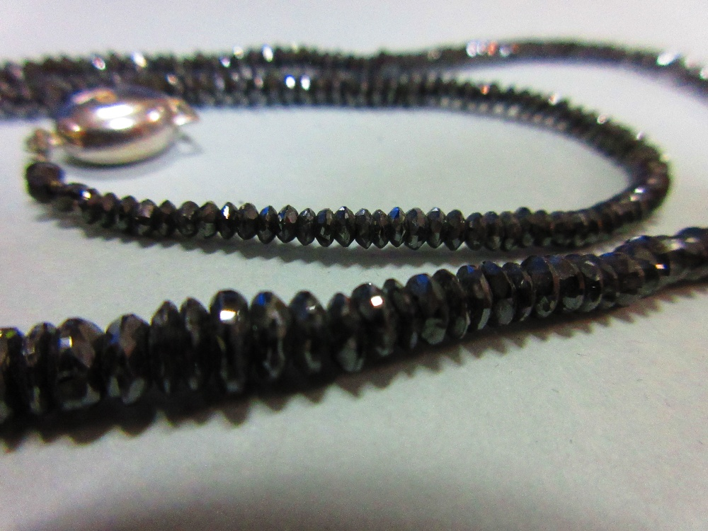 Lot 219 - A black diamond bead necklace, the graduated 2.5 - 5.3mm diameter faceted black diamond beads,