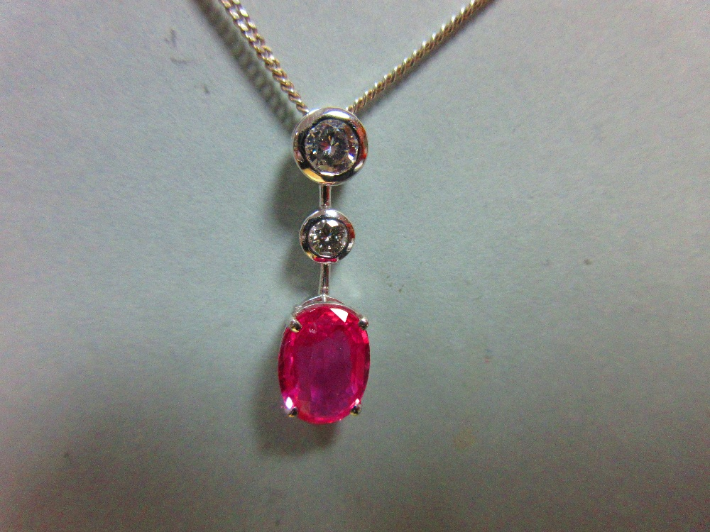 Lot 162 - A pink sapphire and diamond pendant set in 18ct white gold, designed as a line of three stones