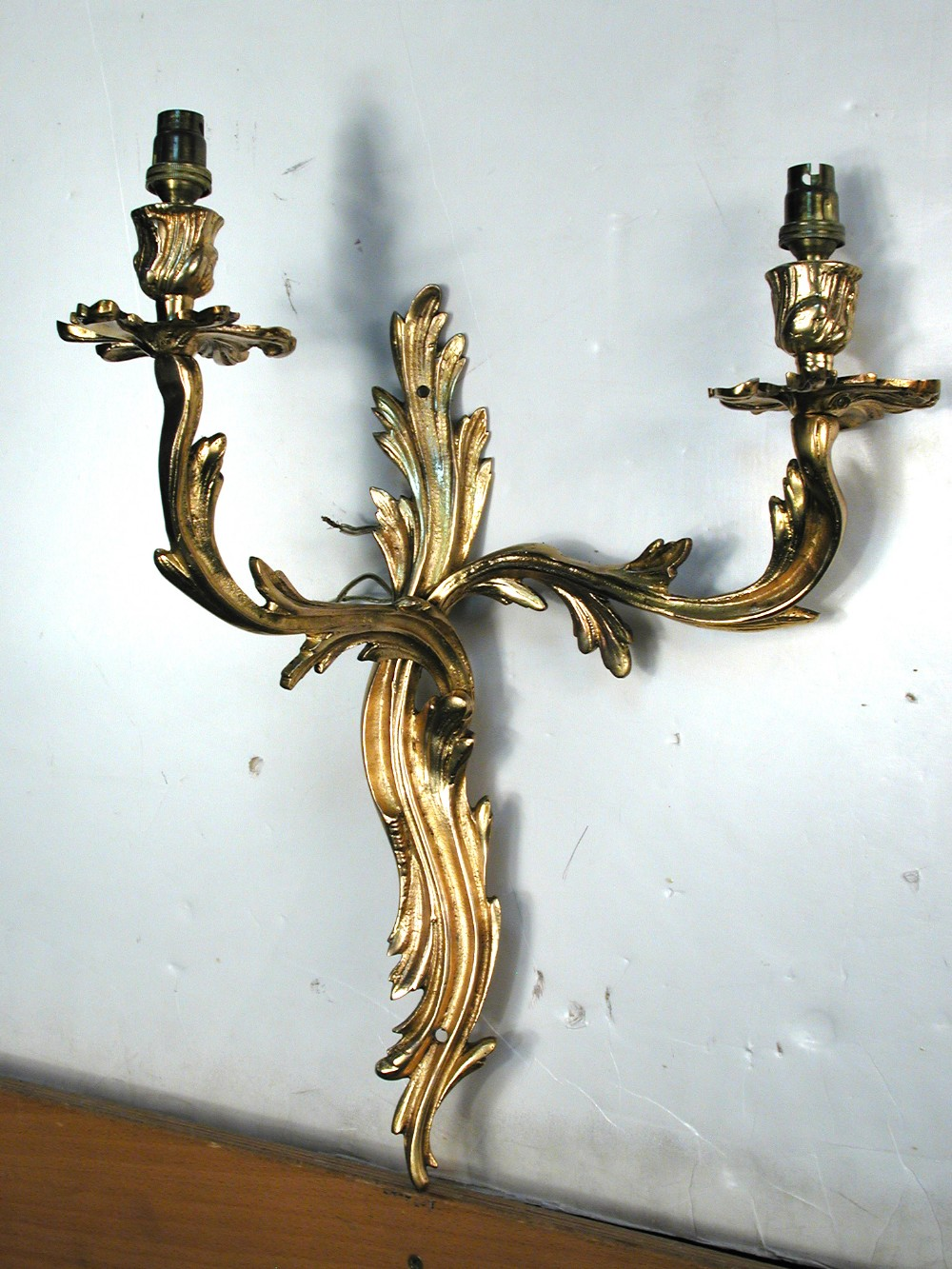 Lot 627 - A set of four Rococo style gilt metal wall lights, the twin-branch lights with scroll-work backs (4)