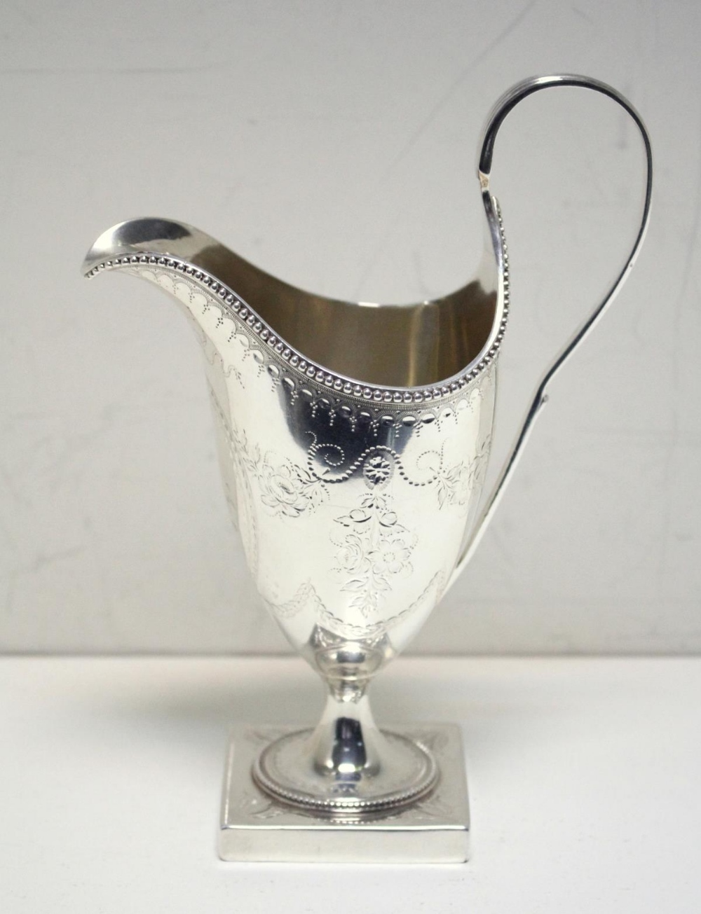 Lot 316 - A George III silver creamer, by Hester Bateman, London 1786, of helmet shape, the body engraved with