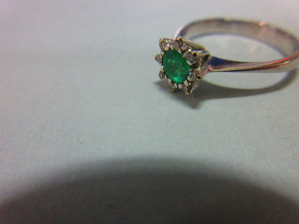 Lot 208 - An emerald and diamond ring, set with a round cut emerald in a small petal border of eight single