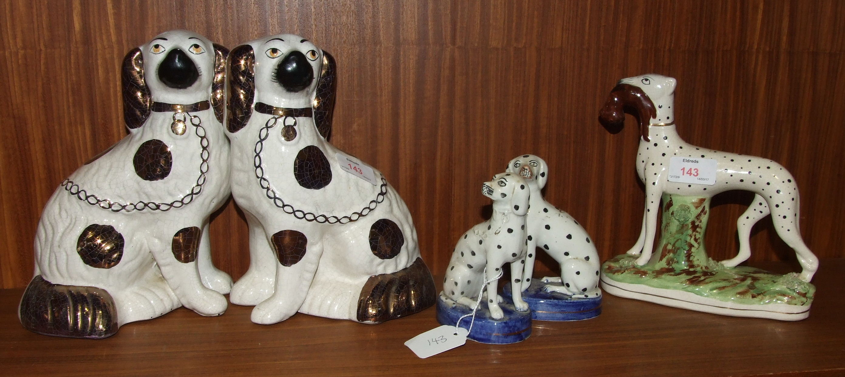 Lot 143 - A Staffordshire standing hound with a hare in it's mouth, on oval base, 19.5cm high, a pair of