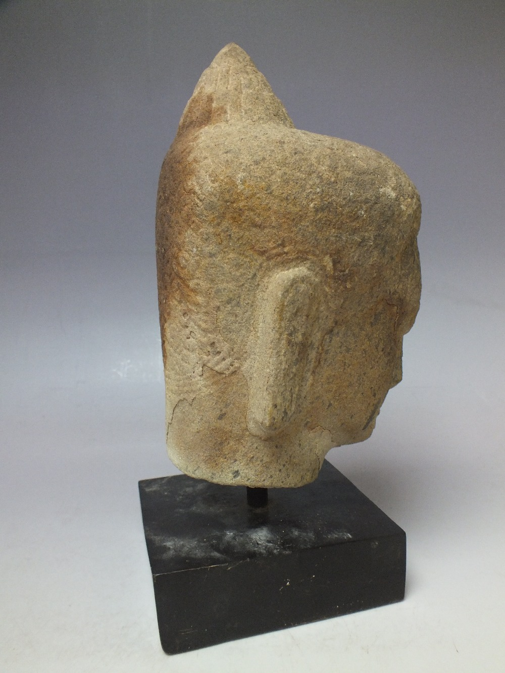 Lot 808 - A CIRCA 13TH CENTURY CAMBODIAN SANDSTONE HEAD, Khumer period, H 19 cm, overall H 25 cm inc base