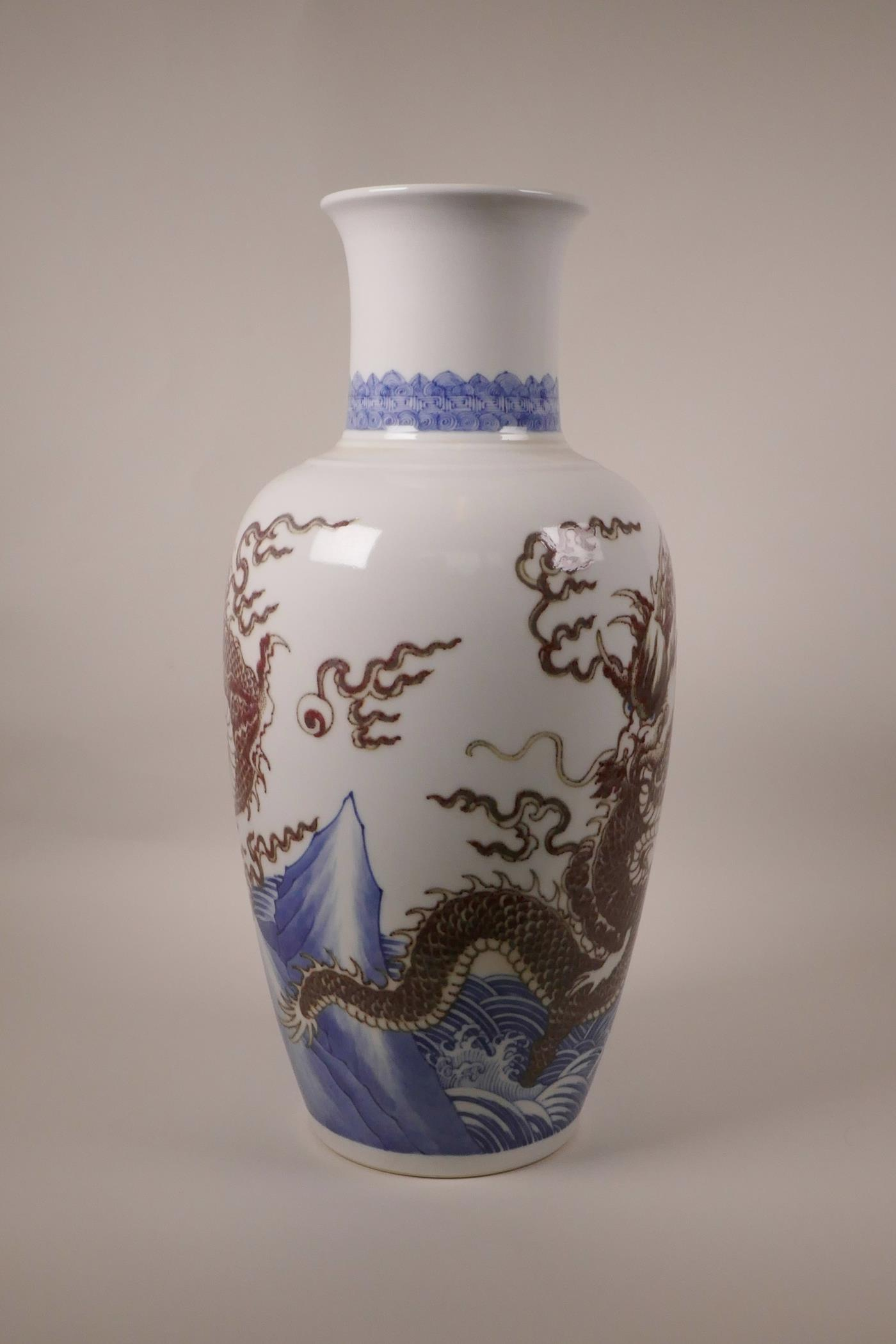 Lot 63 - A large Chinese blue and white porcelain vase decorated with a red dragon chasing the flaming pearl,