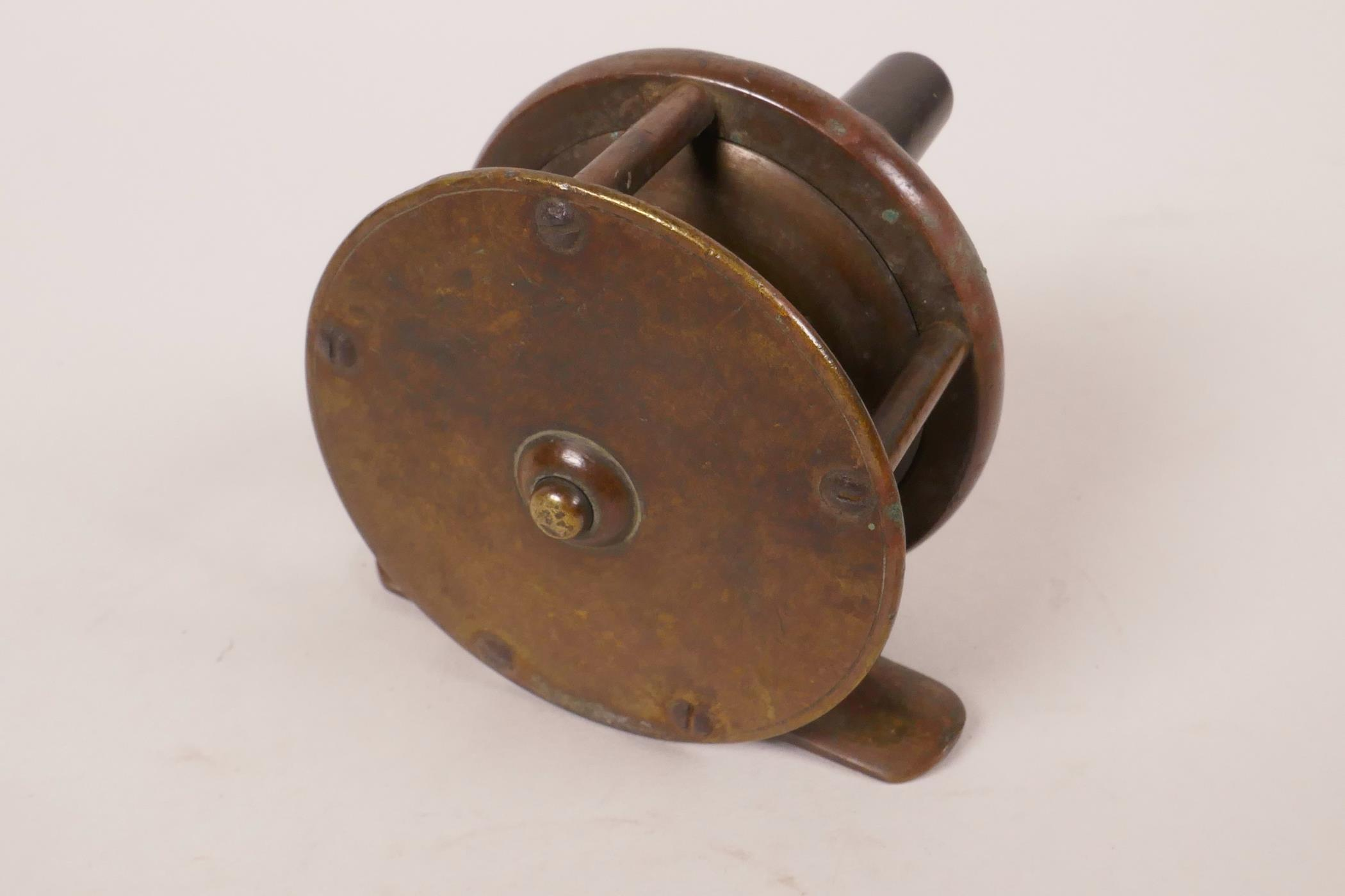 """Lot 25 - A C19th Army and Navy brass trout fishing reel, 2½"""" diameter"""
