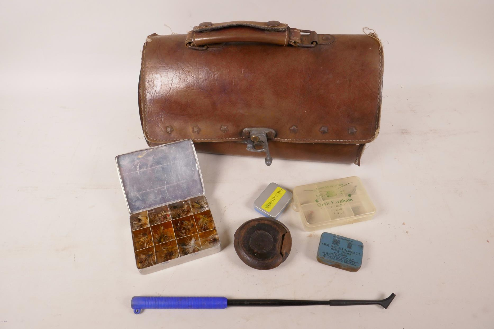 "Lot 39 - A leather bag containing various vintage fishing equipment including fly box and flies, 11"" long"