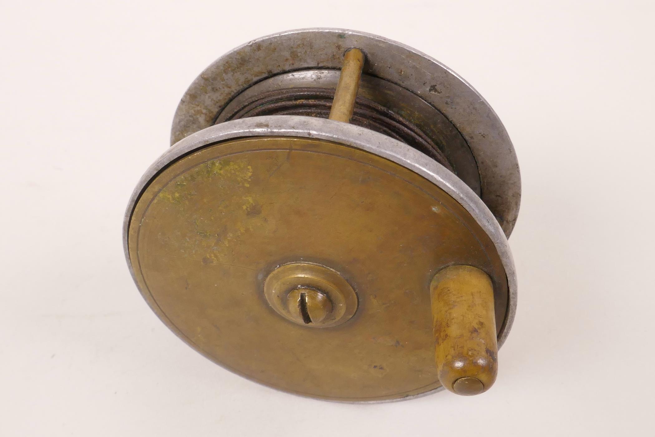 "Lot 10 - A vintage brass and aluminium plate wind fishing reel, 3"" diameter"