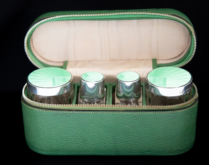 An Art Deco silver and guilloche enamel travelling toilet set including a pair of cologne/perfume