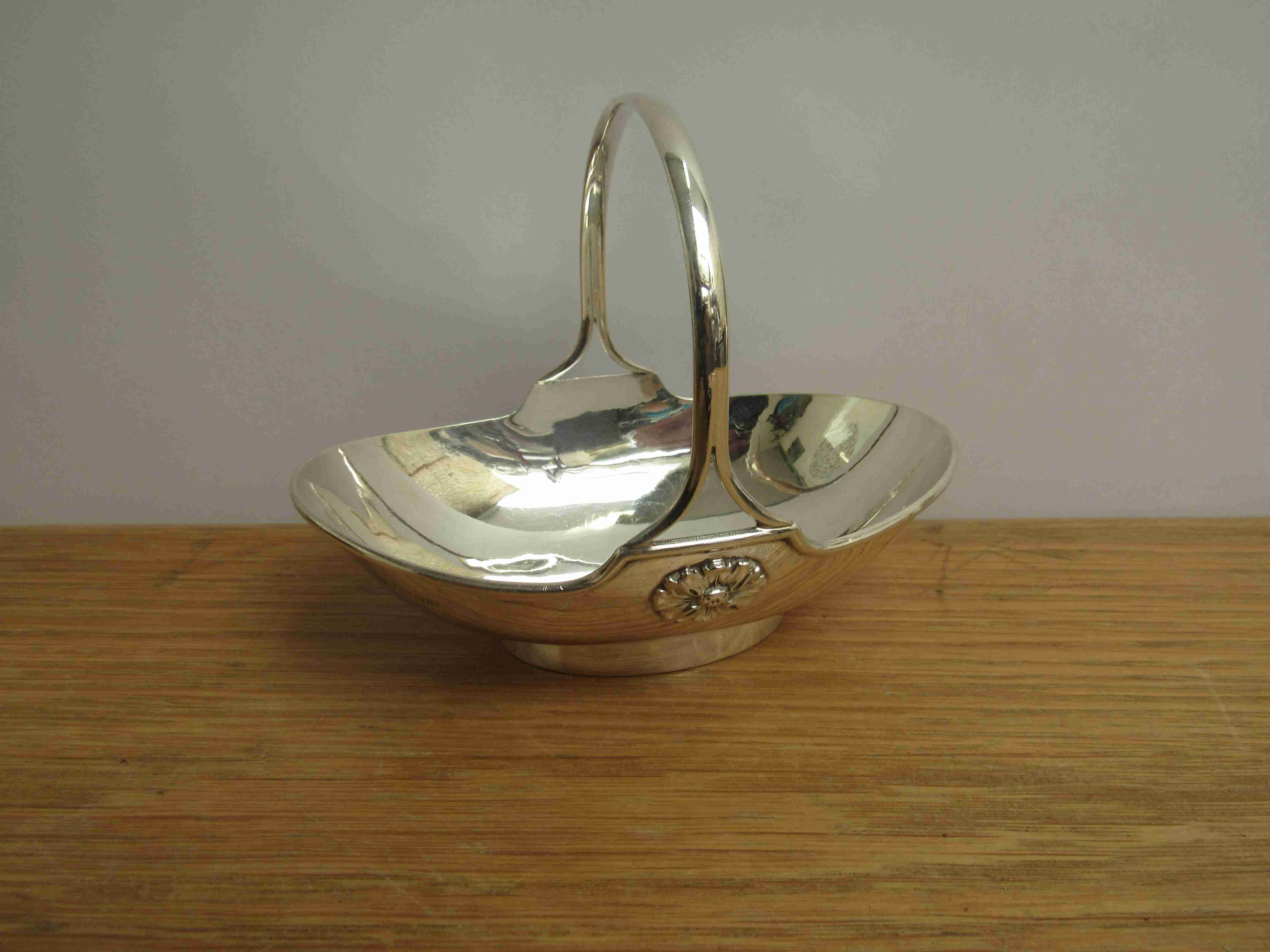 Lot 24 - A Mappin & Webb silver basket with fixed handle of boat form, base set with floral roundels,