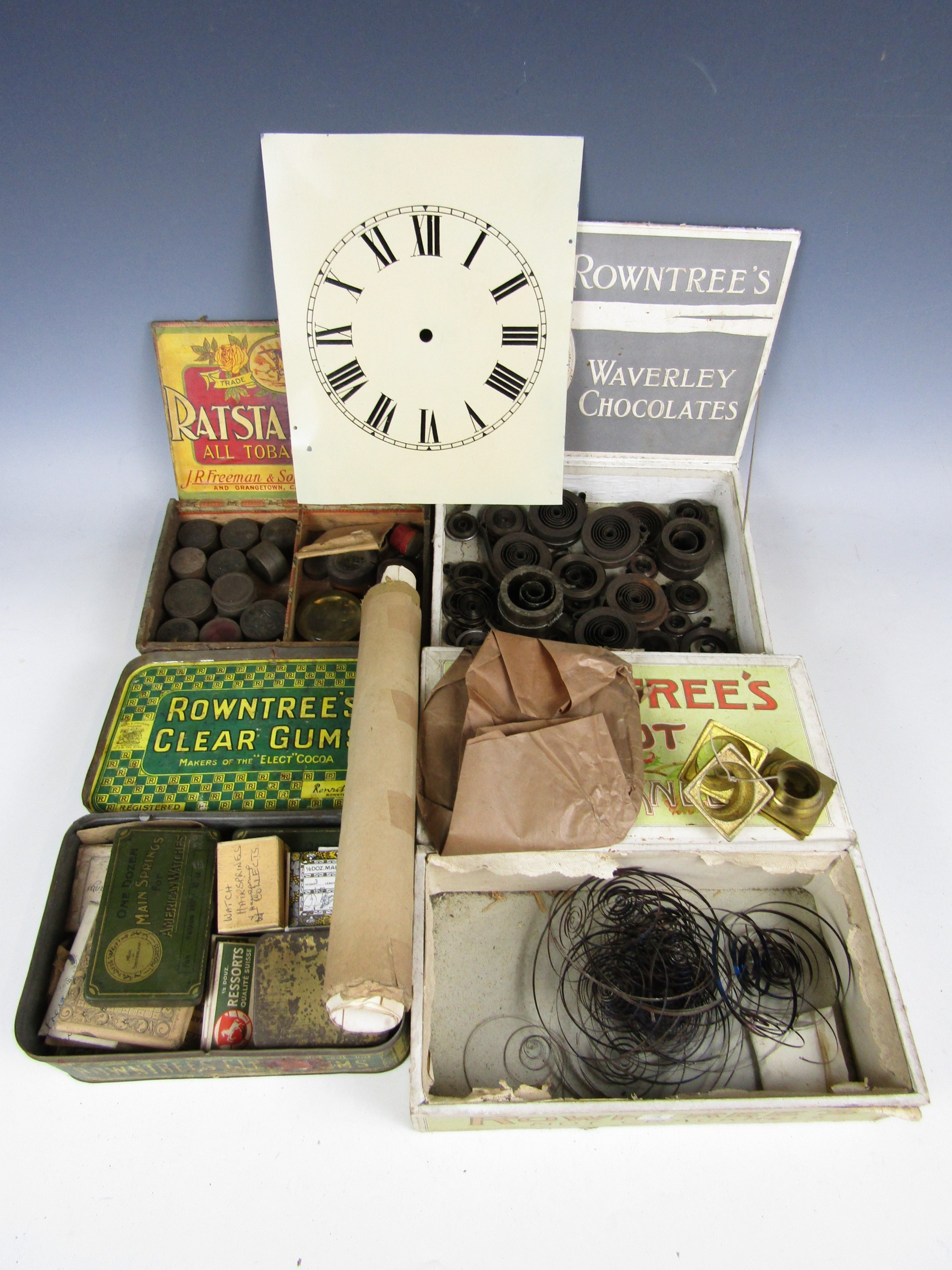 Lot 4 - A quantity of clockmakers and watchmakers' main springs and parts together with a clock dial etc.